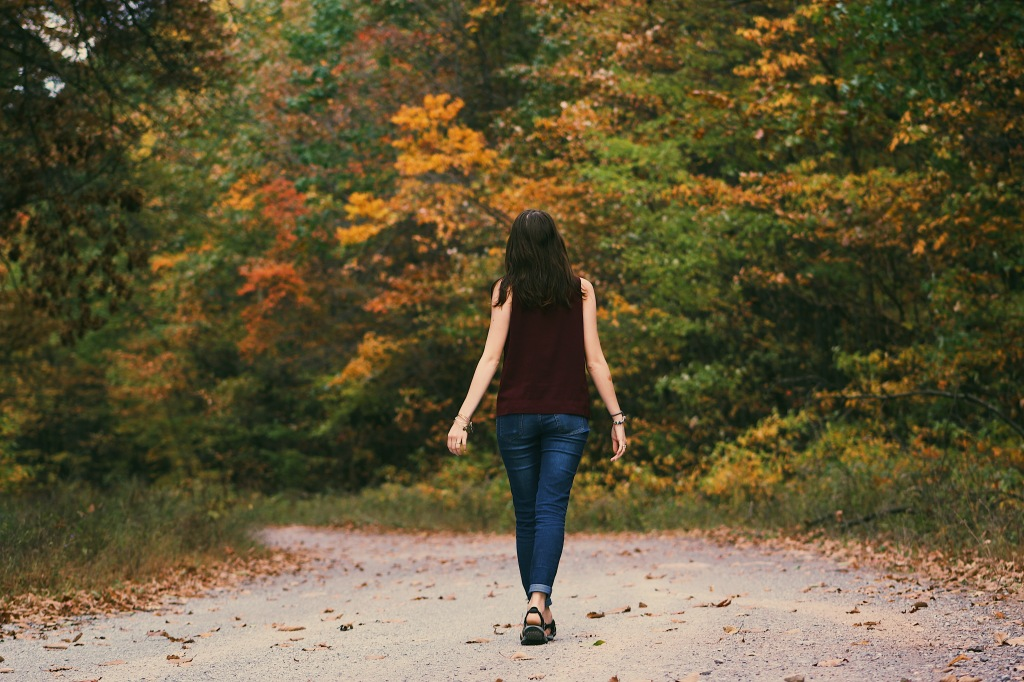 A woman seen from behind, walking on a wide path surrounded by trees in the fall.